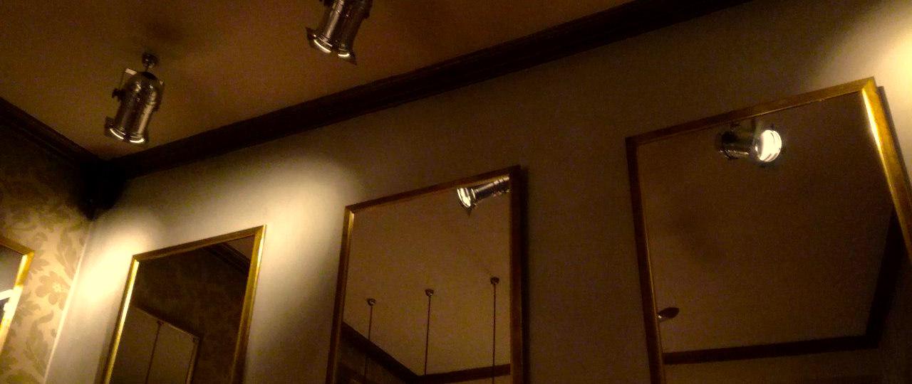 Ansicht des Innenraums der mokkabar nahe der Litcamp-Location: Ein Raum in braun-gold mit großen Spiegeln und Scheinwerfern.